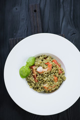 Above view of spinach and tiger shrimps risotto in a white plate