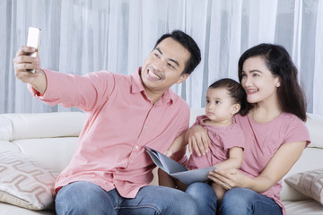 Asian family taking selfie photo at home
