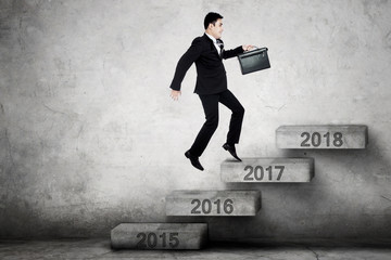 Businessman runs on stairs with number 2017