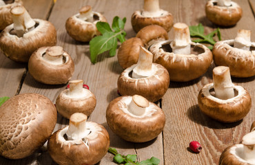 Fresh mushrooms with leaves of arugula on wooden background