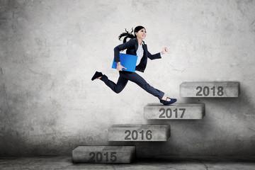 Entrepreneur runs on stairs with folder