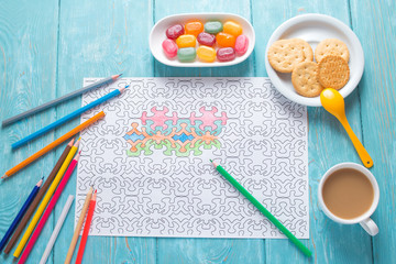White sheet of paper, coloring for adults for rest and relaxation. Blue vintage background, painted wood. Colour pencils. multicolored candies in a saucer and a cup of coffee with milk.
