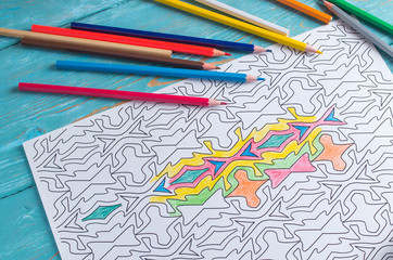 Adult coloring, geometric patterns to paint. On a blue background is a sheet of paper and colored pencils around.