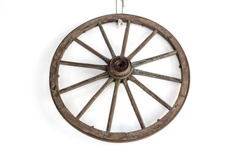 Vintage carriage wheel hang on the white wall / Old wooden wheel / Old wheel hang on the white wall background.
