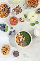 Breakfast set with granola, green smoothie and various of topping. Healthy eating and super foods concept.