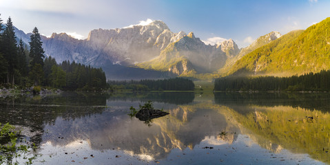 misty morning on the alpine lake laghi di Fusine, Italy