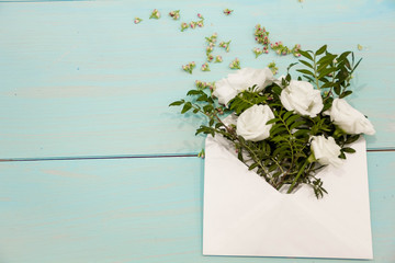 Mothers Day background. Still life, top view, copy space. Unusual creative holiday greeting card. envelope mail with roses bouquet, flat lay. Postcard with empty tag for your text. Square image.