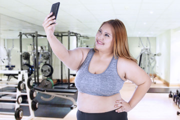 Overweight woman takes selfie photo