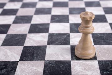 white wooden queen on chessboard
