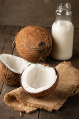Ripe half cut coconut on a wooden background.