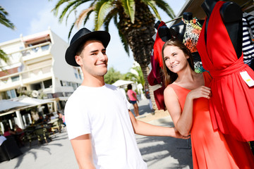 cheerful young couple shopping clothes on seaside promenade walk of a tourist resort