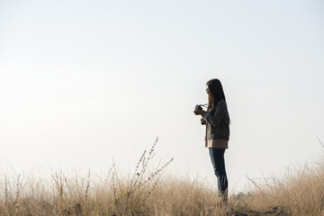 Beautiful woman standing alone among meadow in the evening,she is a photographer,she stand holding the camera prepare take photo.She wearing jacket and blue jean.