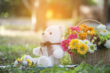 White teddy bear sitting on the grass,with baskets of flowers.