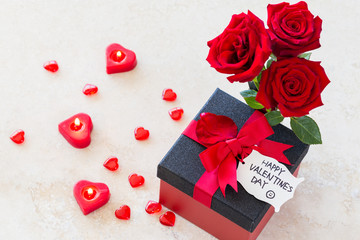 "Valentine gift/Valentines concept with bouquet of roses, heart shaped candles and wrapped gift with ""happy valentine's day"" note on wooden table"