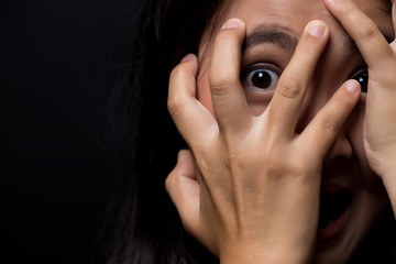 Scared woman on isolated black background