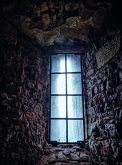 Stone house. Dark room with window