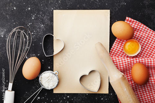 Baking Background With Flour, Rolling Pin, Eggs, Paper Sheet And Heart  Shape On