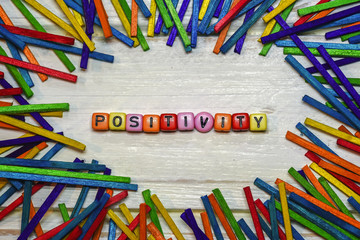dice letters of Positivity word concept with framming colorful wood stick