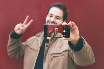 handsome young man taking a selfie with a smartphone, smiling. graded in instagram style. red wall background.