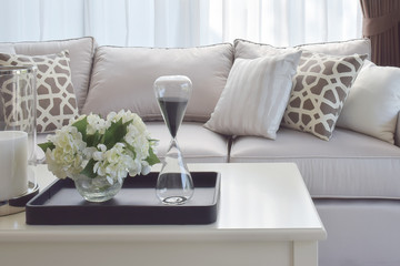 living room design with decorative tray of sand glass and vase on table
