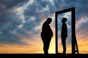 Fat sad man and his reflection in the mirror of a normal man against sky.