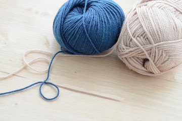 Blue and beige knitting yarn clews on wooden table
