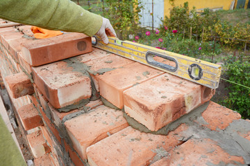 Bricklaying, Brickwork. Close up Bricklaying on House Construction Site. Bricklayer Using a Spirit Level to Check New Brick Wall Outdoor. Bricklaying  Masonry. Brick masonry. Bricklaying Stock Photo.
