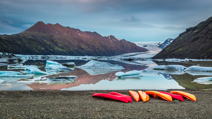 Kayaks at glacial lake in the mountains, Iceland in summer