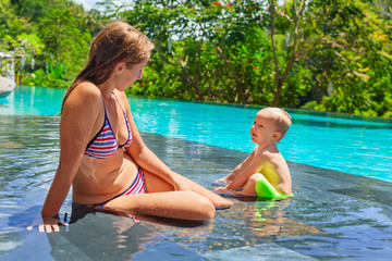 Family beach holiday concept. Happy son with mother - active baby have fun at pool side in infinity swimming pool. Summer healthy lifestyle and children water activity, games and lessons with parents.