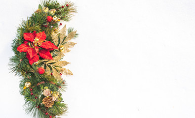 Christmas holiday faux poinsettia pine wreath adorned with gold leaf ribbon, Christmas balls and holly, resting on natural snow with white copy space.