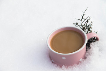 cappuccino in a pink cup on the snow