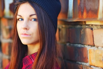 Young cute brunette girl with long hair, dressed in a plaid shirt and black hat looks and smiles, standing near a brick wall at sunset.