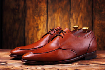Fashionable leather derby shoes for men on wooden background