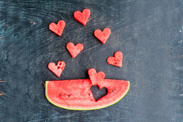 Piece of watermelon and hearts on the old wooden background. Flat lay