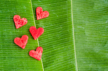 watermelon hearts at the background of banana leaves. Flat lay