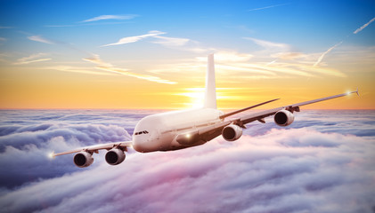 Huge airplane flying above clouds in dramatic sunset