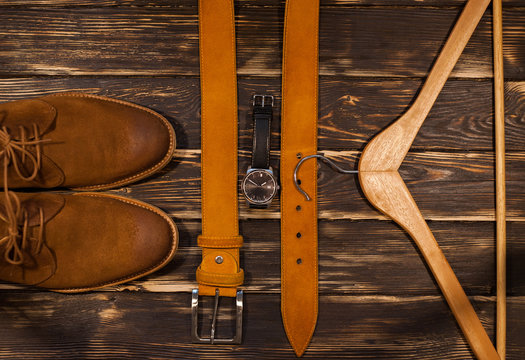 Brown men's boots,  leather belt and hanger on wooden background.