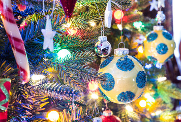 Christmas tree decorations.  Yellow ball with blue spots, shiny silver ball, big and small.  Holiday decoration balls hang on a small faux indoor Christmas tree, bathed in colored lights.
