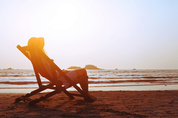 happy summer beach holidays, woman relaxing in deckchair at sunset