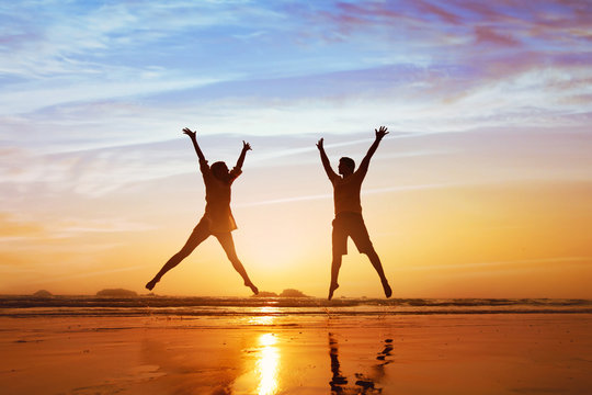 happy couple jumping on the beach at sunset, family summer holidays or honeymoon