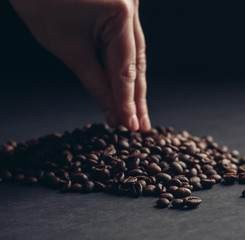 coffee, coffee beans are in hand, the coffee beans on a dark background