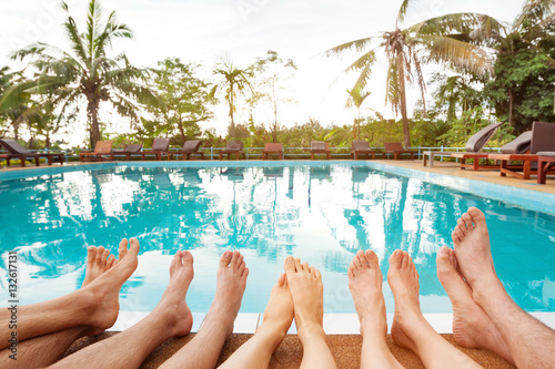 Family Relaxing Near Swimming Pool In Hotel Feet Of Group Of Friends Or Parents With Children