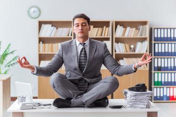 Handsome meditating on the office desk