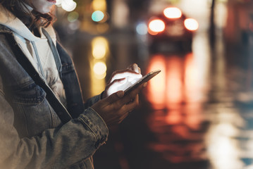 Girl pointing finger on screen smartphone on background illumination bokeh color light in night atmospheric city, hipster using in hands and texting mobile phone, mockup taxi street, content lifestyle