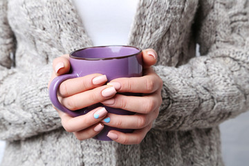 Woman hands with manicure holding cup of coffee