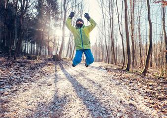 Happy active boy jumps in frozen park