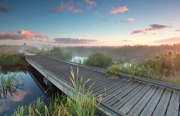 wooden biking bridge over river at sunrise