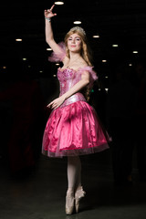 Young woman cosplayer wearing pink dress posing