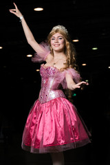 Young woman cosplayer wearing pink dress posing