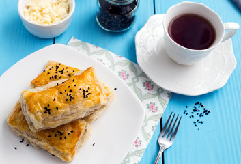 Homemade cheese puff pastries and cup of tea on blue wooden background